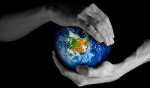 mains tenant la planète Terre